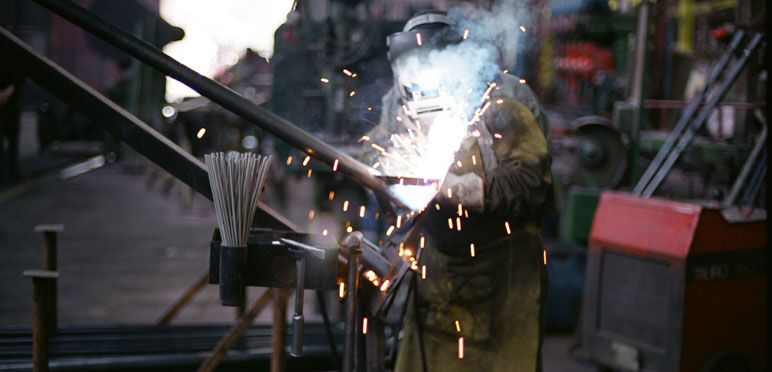 Person works with safety equipment and sparks fly. From Crometal Cooperative Argentina.
